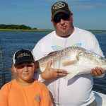 Father and Son hold Bull Redfish on Semper Fi Charters Fishing Boat