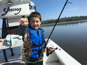 Kid holds fish he caught while having some Amelia Island Inshore Fishing Fun