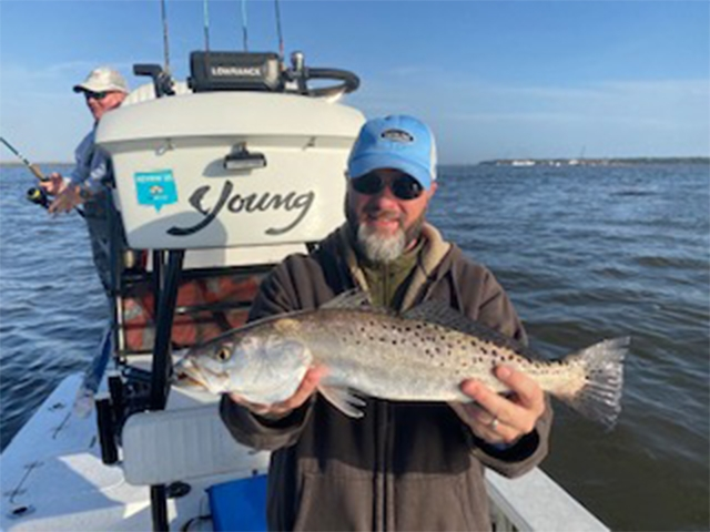 Happy Fisherman holding Speckled Trout on Charter Fishing Boat at Amelia Island